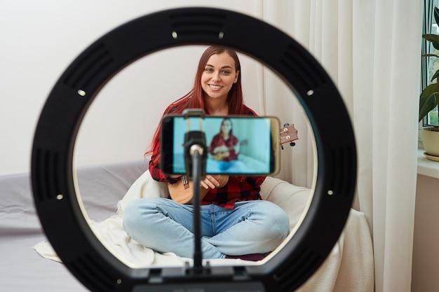 Widok przez lampę pierścieniową bloger muzyk nagrywa transmisję online na telefonie komórkowym, w której kobieta gra na ukulele dla swoich zwolenników