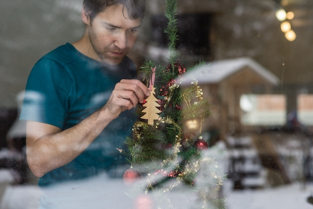 Widok przez okno młodego człowieka wiszącego drewnianego drzewa na choince z odbiciem zimowej przyrody w szkle.