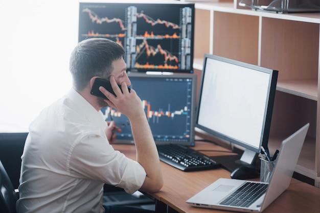 Widok przez ramię i makler giełdowy prowadzący transakcje online podczas przyjmowania zleceń przez telefon. wiele ekranów komputerowych pełnych wykresów i analiz danych w tle