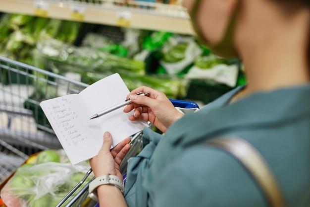 Widok przez ramię kobiety zaznaczającej pozycje listy zakupów za pomocą pióra podczas kupowania produktów w supermarkecie