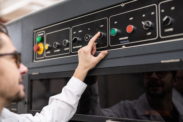 Widok przez ramię młodego operatora wciskającego przycisk na panelu sterowania podczas pracy w zautomatyzowanym przemyśle