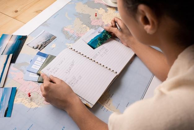 Widok przez ramię turysty sprawdzającego notatki w dzienniku podczas planowania miejsc do odwiedzenia oglądając zdjęcia
