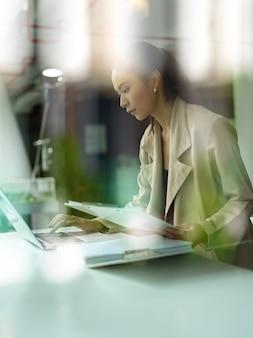 Widok przez szklane okno pracownica biura, koncentrując się na swoim zadaniu z laptopem i papierkową robotą