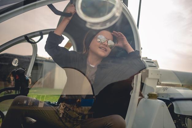 Widok przez szybę kokpitu helikoptera wesołej dziewczyny z nastolatką patrzącą w niebo