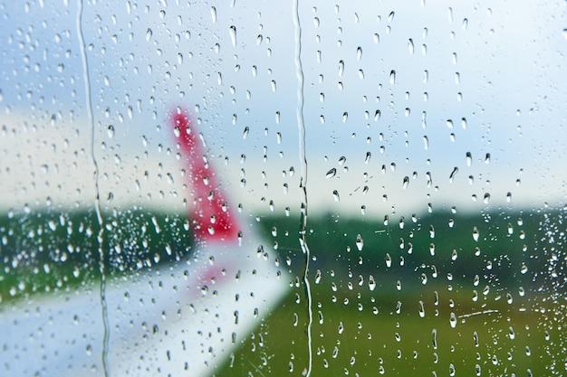 Widok przez zamgloną szybę samolotu przed startem w deszczowy dzień