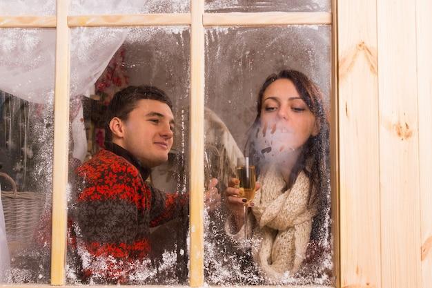 Widok przez zimne oszronione okno młodej pary świętującej w zimowej kabinie, delektującej się drinkiem i dmuchającej w szybę, aby skondensować oddech na mrozie