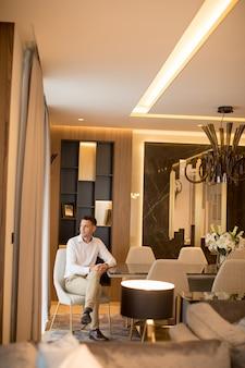 Widok przy przystojnym welldressed mężczyzna obsiadaniem w luksusu domu wnętrzu