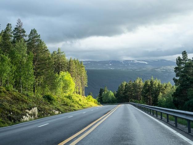 Widok pustej drogi asfaltowej z podwójnymi żółtymi liniami.