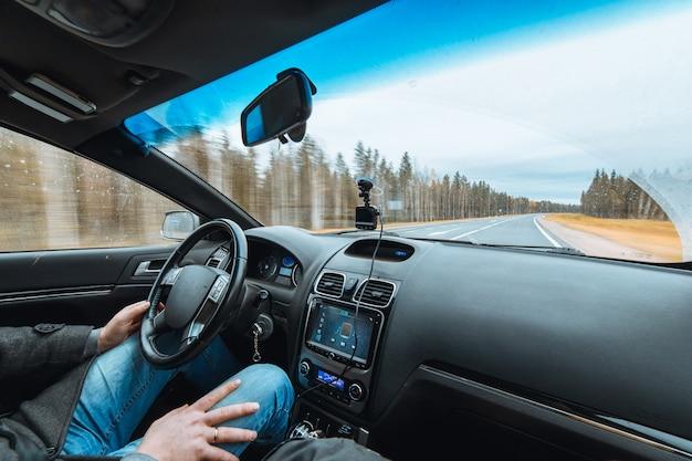 Widok pustej drogi i lasu przez przednią szybę samochodu. wysoka prędkość jazdy