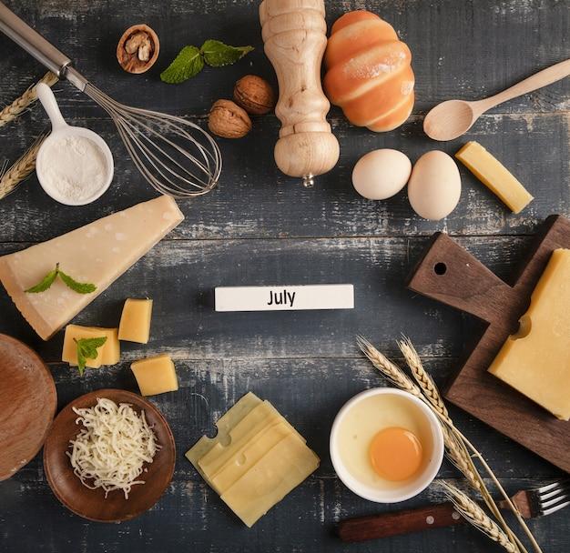 """Widok pysznego półmiska serów z orzechami włoskimi, jajkami i mąką na stole z napisem """"lipiec"""""""