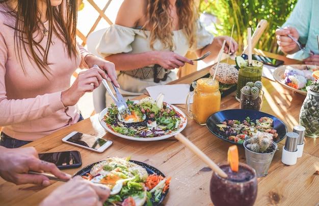Widok rąk młodych ludzi, którzy jedzą brunch i piją koktajle miskę ze słomkami ekologicznymi w modnej restauracji barowej. zdrowy styl życia, koncepcja trendów żywności