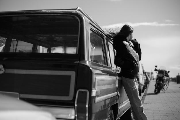 Widok ramy. czarno-białe zdjęcie na zewnątrz. widok z tyłu hipster dziewczyny z dmuchaniem włosów.