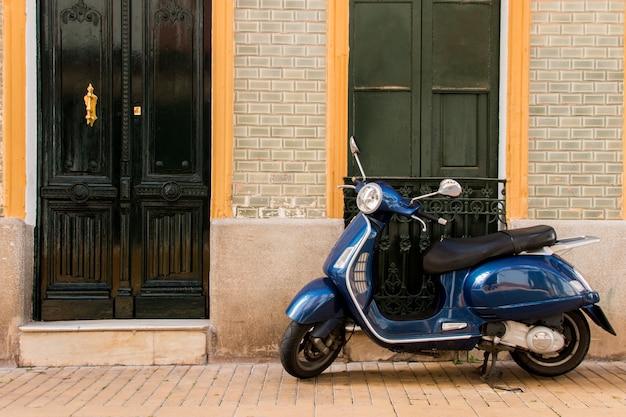 Widok rocznika hulajnoga vespa zaparkowany na hiszpańskim mieście.