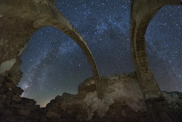 Widok rozgwieżdżonego nieba i drogi mlecznej z wnętrza sklepienia zrujnowanego kościoła