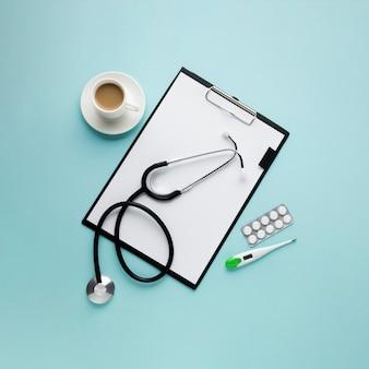 Widok schowka z papierem i filiżanką kawy pod dużym kątem; termometr; stetoskop; blister pakowany w lek na niebieskim tle