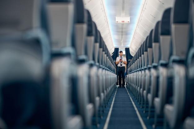 Widok siedzeń pasażerskich linii lotniczych w kabinie samolotu, podczas gdy mężczyzna stojący na górze przejścia a