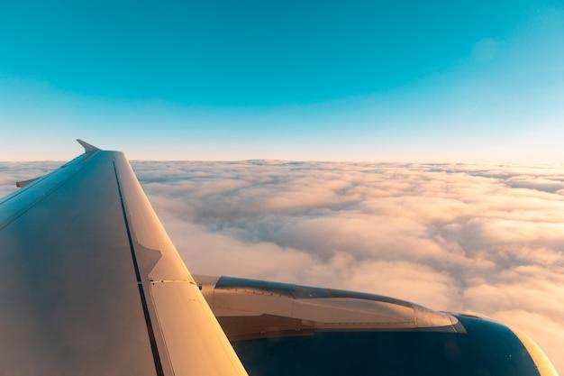 Widok skrzydła samolotu nad chmurami z okna