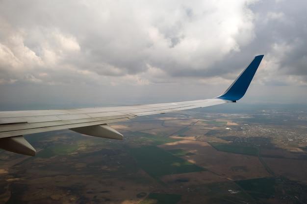 Widok skrzydła samolotu odrzutowego lądowania na lotnisku przy złej pogodzie. koncepcja transportu i transportu lotniczego.