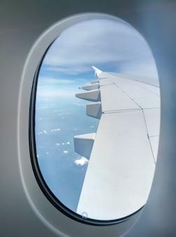 Widok skrzydła samolotu pasażerskiego z iluminatora na niebie