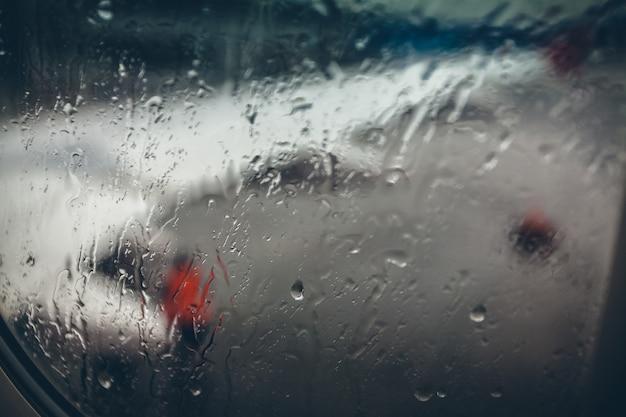 Widok skrzydła samolotu w deszczowy dzień przez okno z kroplami wody