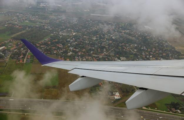 Widok skrzydła samolotu z samolotu na niebo, chmury, ziemię z wysokości lotu.