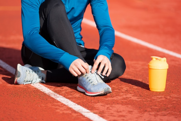 Widok sportowca wiążącego sznurówki do butów z bliska. mężczyzna zaciskając sznurówki do butów siedzi na ziemi na bieżni.