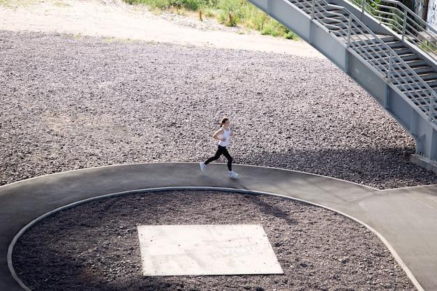 Widok sportsmenki biegnącej wzdłuż toru