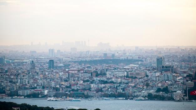 Widok stambułu przy pochmurnej pogodzie, wiele niskich i wysokich budynków, mgła, cieśnina bosfor na pierwszym planie, turcja