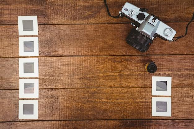 Widok stara kamera z fotografiami ono ślizga się na drewnianym biurku