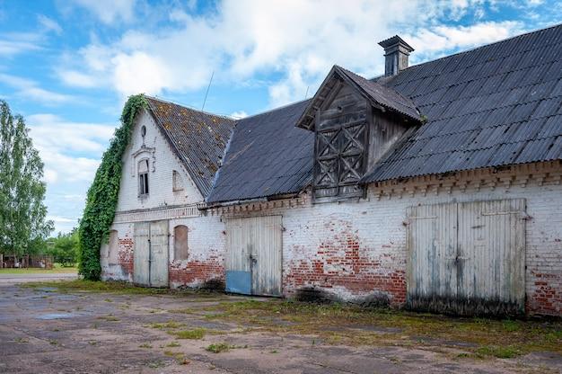 Widok starej opuszczonej stodoły z cegły w okresie letnim.