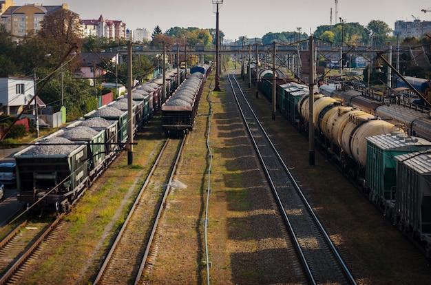 Widok starej zakurzonej kolei z wagonami towarowymi i liniami energetycznymi