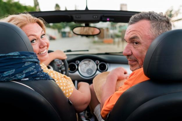 Widok starszej pary turystów na wakacjach w samochodzie z tyłu