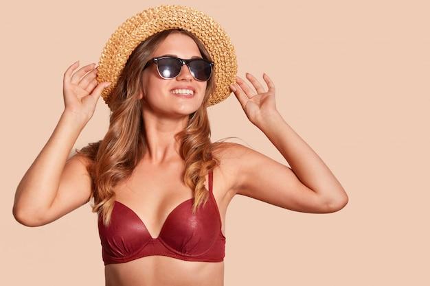 Widok studyjny wesołej kobiety z zębatym uśmiechem, ubrany w czarne okulary przeciwsłoneczne, słomkowy kapelusz, czerwony kostium kąpielowy, wygląda w oddali, na beżowym tle, wolne miejsce na treści promocyjne.