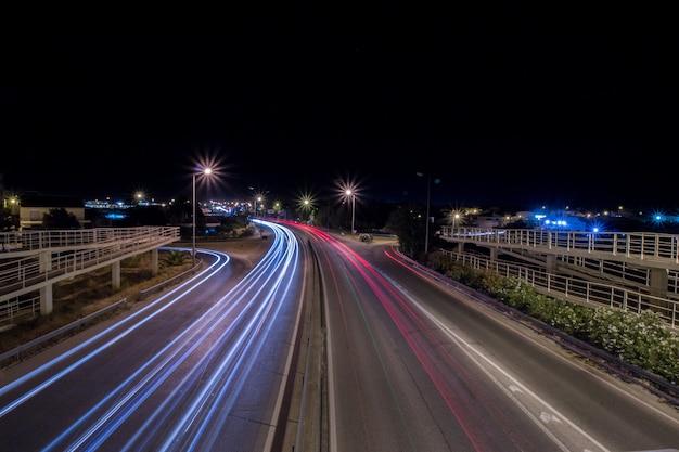 Widok świateł smuga samochodu w nocy w pobliżu lotniska miasta faro, portugalia.