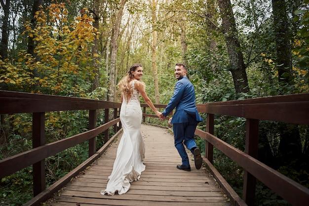 Widok świeżo poślubionej pary biegnącej i patrząc wstecz na most w lesie z tyłu