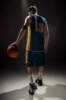 Widok sylwetka koszykarza posiadającego piłkę do koszykówki na czarnej przestrzeni