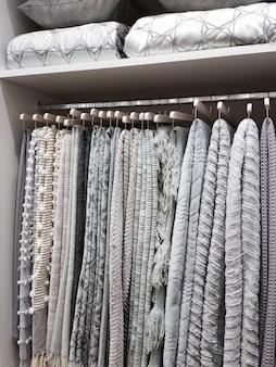 Widok szafy z wełnianymi kocami wiszącymi na wieszakach oraz poduszkami i kocami na półkach.