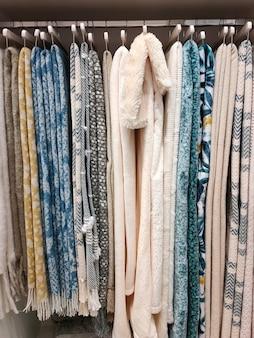 Widok szafy z wiszącymi na wieszakach wełnianymi kocami. koncepcja domu, styl życia.