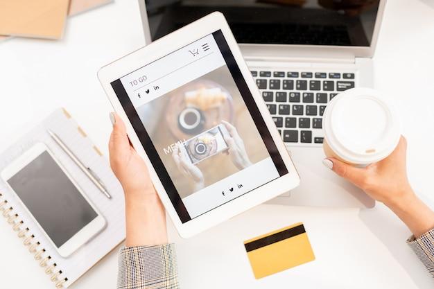 Widok tabletu z wygaszaczem ekranu sklepu internetowego prowadzonego przez bizneswoman z drinkiem w miejscu pracy