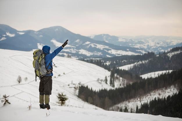 Widok turystycznego turysty w ciepłej odzieży z plecakiem stojącym z podniesionymi rękami na górskiej polanie na tle przestrzeni kopii drzewiastego grzbietu górskiego i pochmurnego nieba z tyłu.