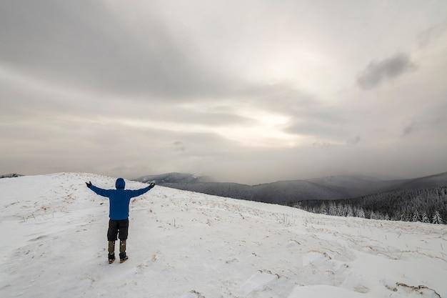 Widok turystycznego turysty w ciepłej odzieży z plecakiem stojącym z podniesionymi rękami na polanie pokrytej śniegiem na górze lasu świerkowego i zachmurzonym niebie z tyłu.