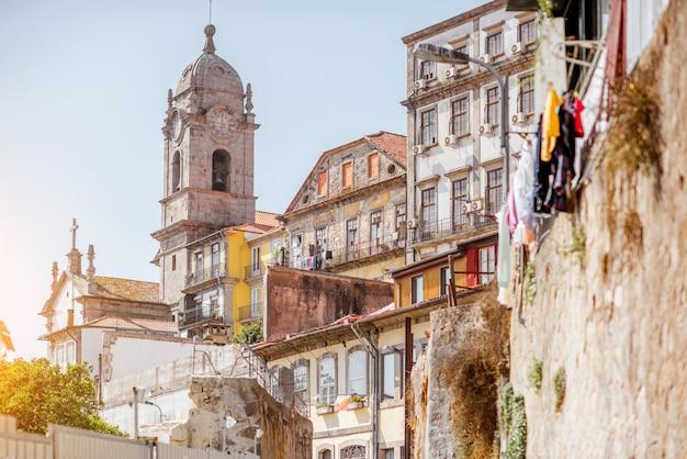 Widok ulicy na piękne stare budynki i wieżę kościoła w mieście porto, portugalia