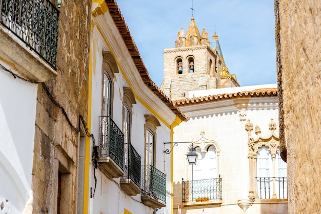 Widok ulicy ze starą wieżą katedry w mieście evora, portugalia