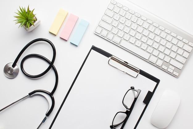 Widok urządzeń bezprzewodowych pod dużym kątem; okulary w schowku; stetoskop i notatki samoprzylepne na białym stole