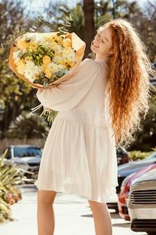 Widok uśmiechnięta kobieta na zewnątrz z bukietem wiosennych kwiatów z tyłu