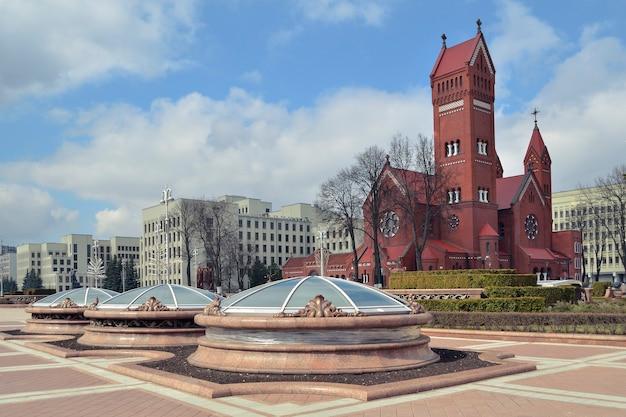 Widok w słoneczny dzień na plac niepodległości i słynny czerwony kościół w mińsku