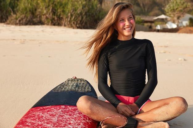 Widok wesołej kobiety siedzi ze skrzyżowanymi nogami, zadowala zadowolony wyraz twarzy