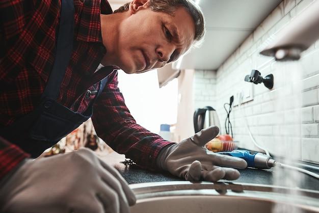 Widok wewnątrz zbliżenie przystojny hydraulik naprawiający zlew w kuchni