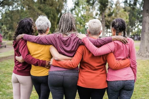 Widok wielopokoleniowych kobiet, które bawią się razem na świeżym powietrzu w parku miejskim z tyłu