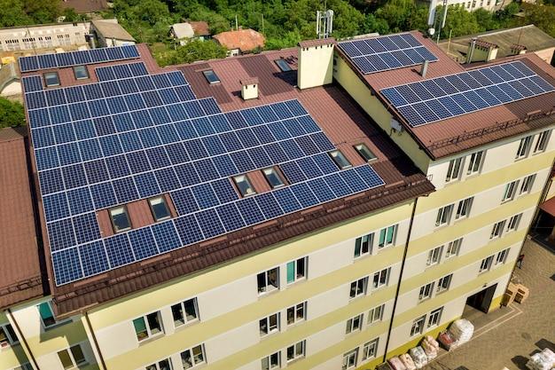 Widok wielu paneli słonecznych zamontowanych na dachu budynku przemysłowego.